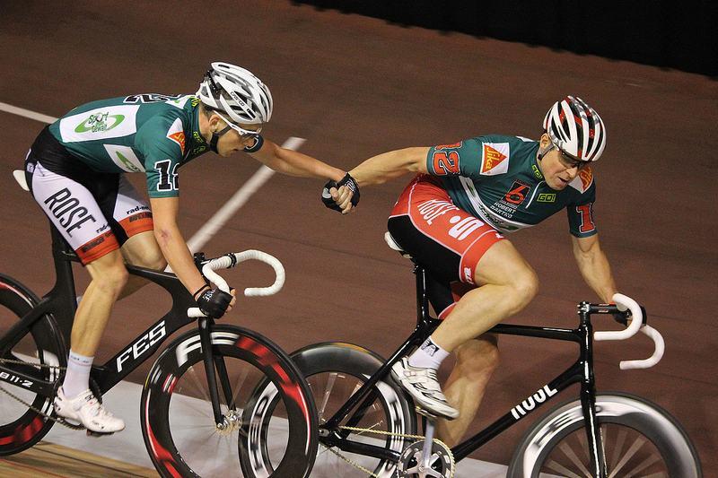 Zwei Radrennfahrer reichen sich währen der Fahrt die Hände.