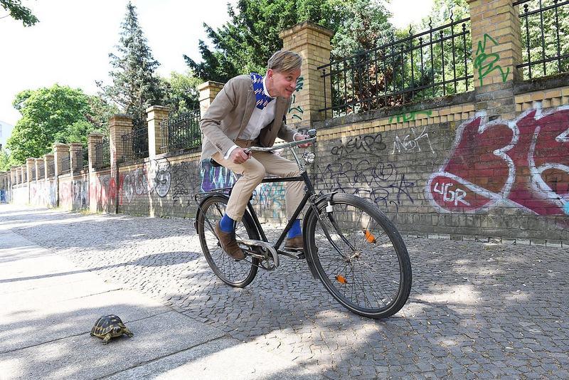 Wettrennen zwischen einer Schildkröte und einem Mann auf einem Fahrrad.