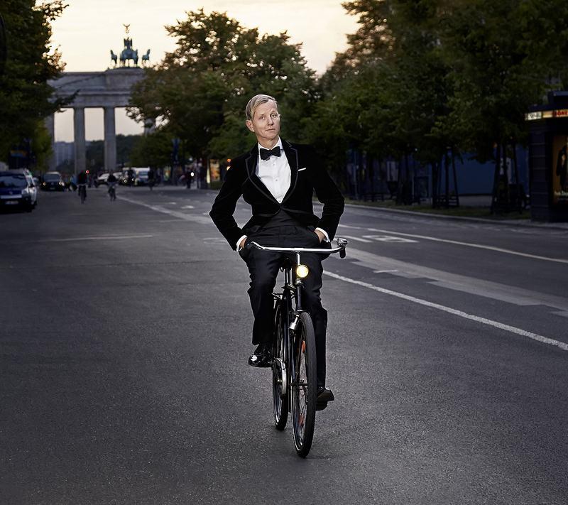 Mann in einem Smoking fährt mit den Händen in den Hosentaschen Rad.