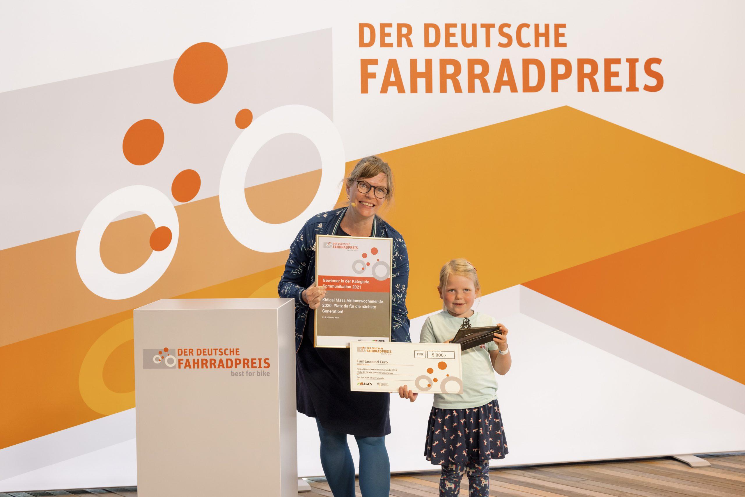 Simone Kraus nimmt mit Ihrer Tochter den 1. Preis für die Kidical Mass entgegen.