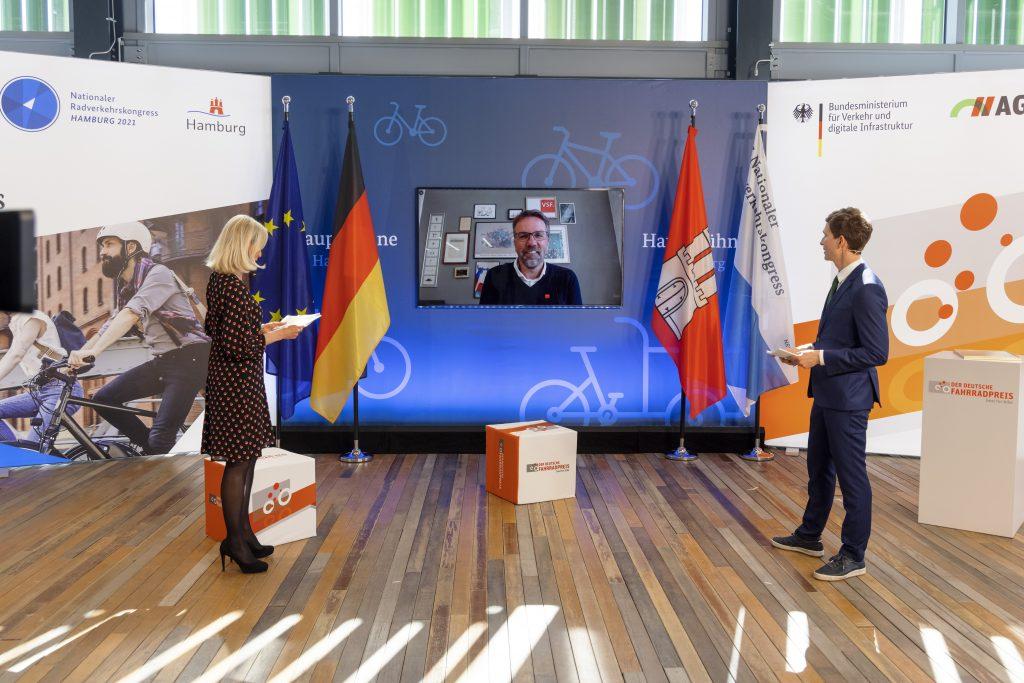 Laudator Uwe Wöll, Geschäftsführer Verbund Service und Fahrrad e.V. übergibt symbolisch den 1. Platz beim Fotowettbewerb.