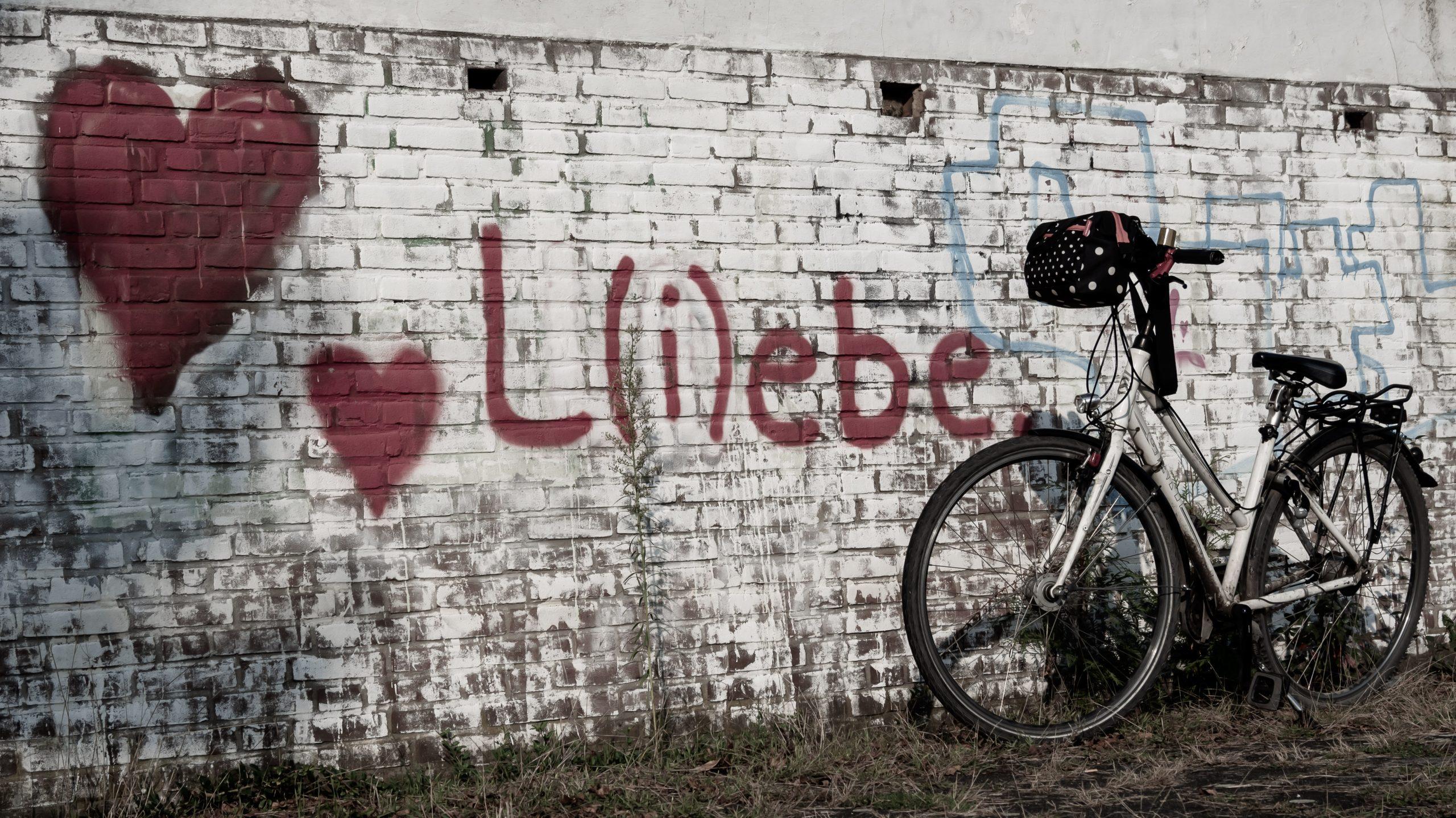 Herz mit der Aufschrift Liebe an einer Mauer mit einem Fahrrad davor.